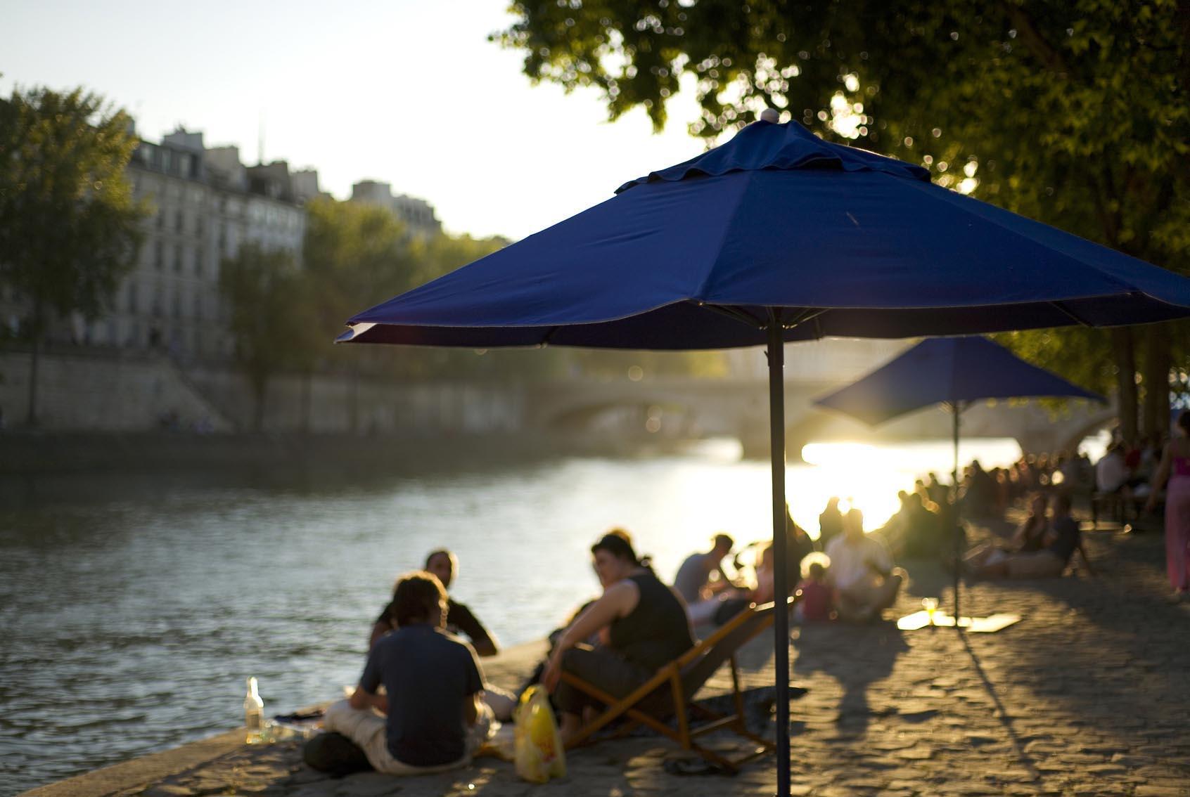 Des personnes prennent le soleil au bord de la seine, les pieds dans le sable.
