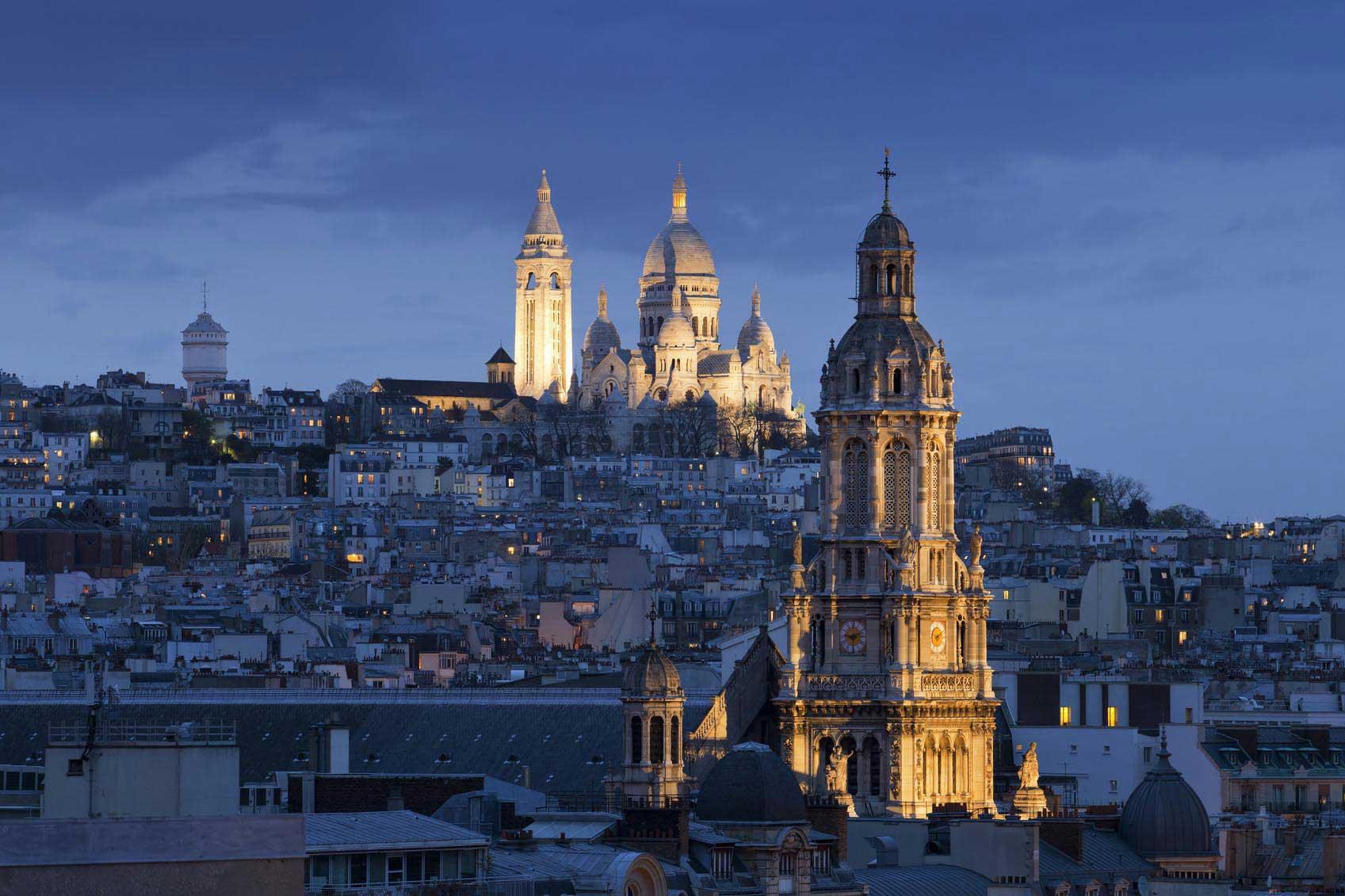 La Basilique du Sacré-Cœur illuminée en pleine nuit, dans les hauteurs de Montmartre.