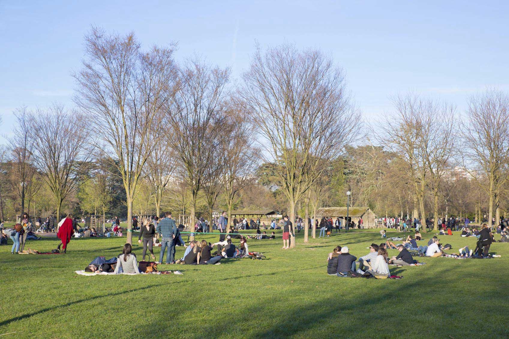 De nombreuses personnes se détendent dans l'herbe du parc de la Tête d'Or