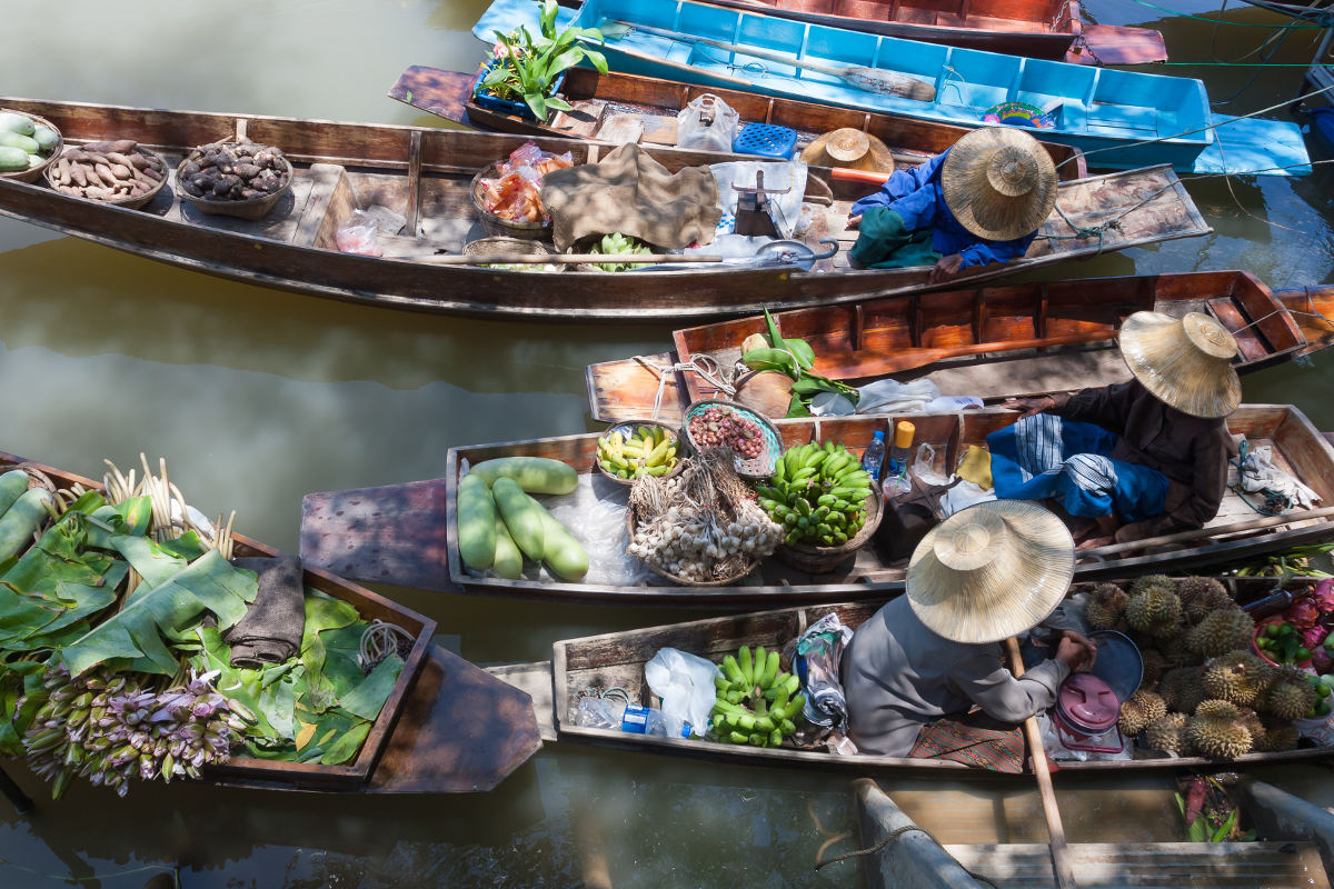 bangkok floating market's vendors on boats with fruits and vegetables