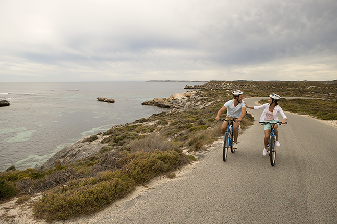 Young couple riding bikes along Rottenest Island bike paths