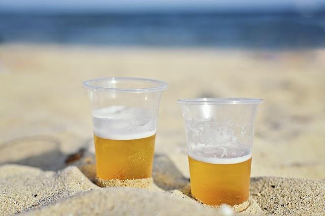 Segurando um copo de cerveja na praia