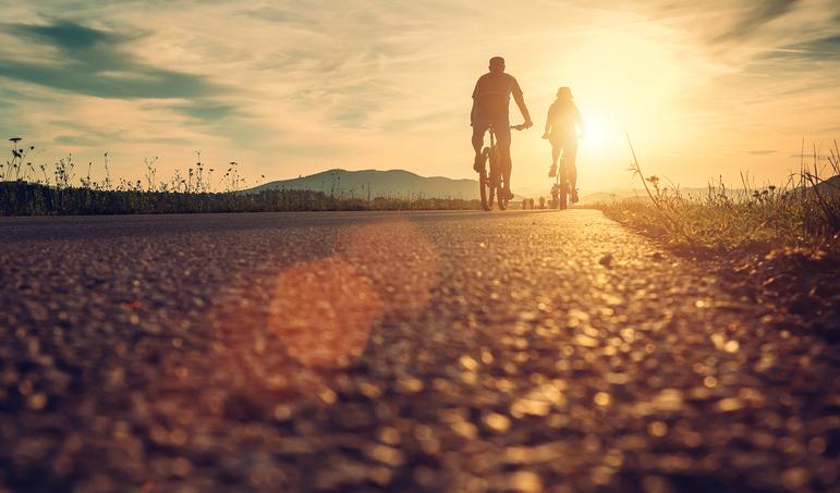 Jovens pedalando ao pôr do sol