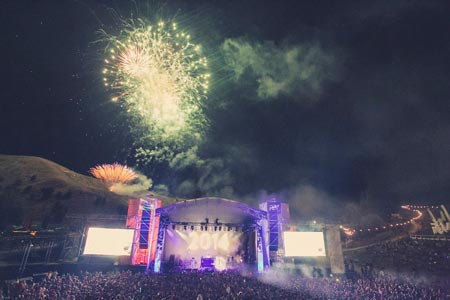 Night Time shot w/ purple stage with green fireworks overhead