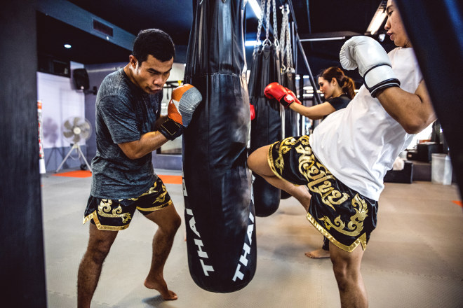 Muay Thai trainer holding long practice bag for trainee to kick